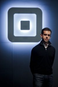 Jack Dorsey stood infront of Square logo