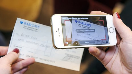 A mobile phone taking a picture of a cheque